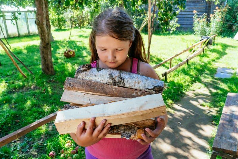 registros de madera del control de la mano de la niña un brazado de leña imágenes de archivo libres de regalías