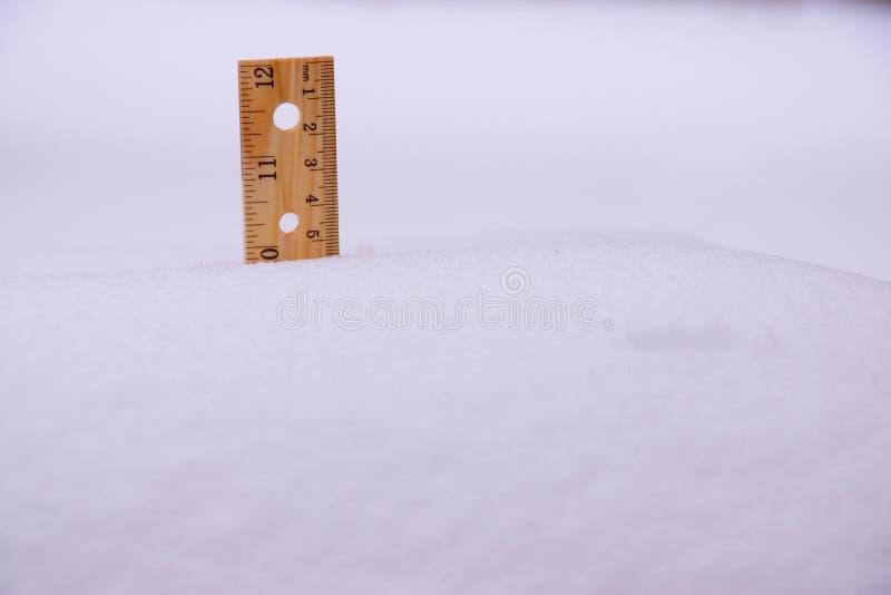 Regla en nieve diez pulgadas foto de archivo libre de regalías