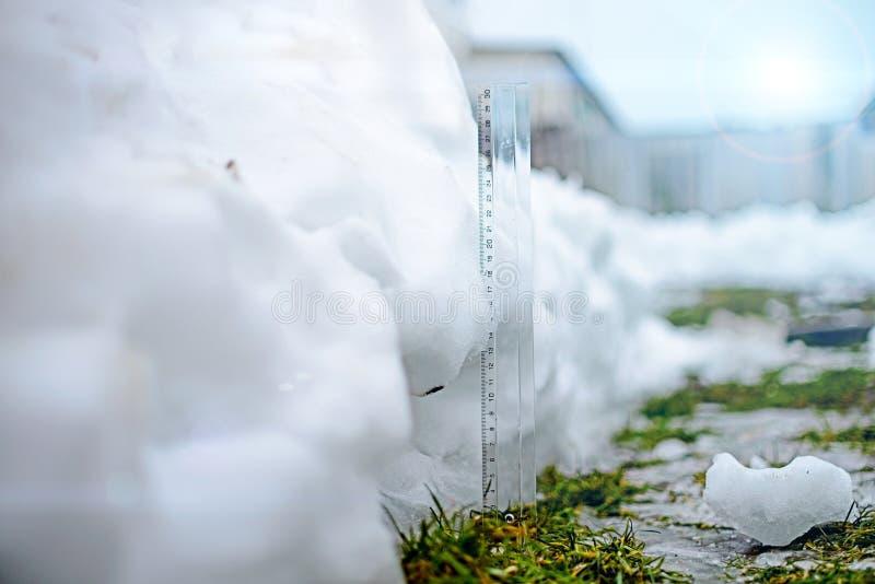 Regla que mide el grueso de la nieve tono imagen de archivo