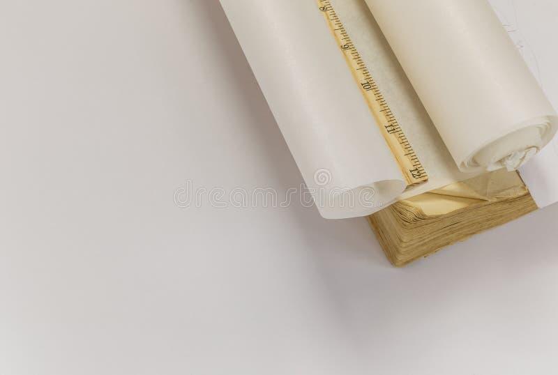 Regla, rollo del papel de trazo y libro viejo foto de archivo