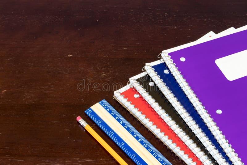 Regla y lápiz coloreados multi de los cuadernos en una tabla fotos de archivo