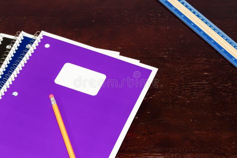 Regla y lápiz coloreados multi de los cuadernos en una tabla fotografía de archivo libre de regalías