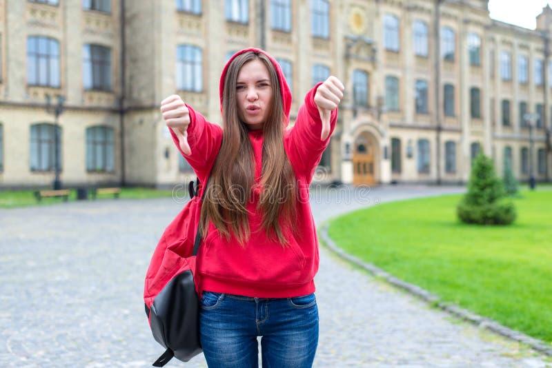 Regler bryter begrepp Foto av att slå som uttrycker hennes tonåriga rebelliska hipster för harm i hoodien som visar fingrar ner s arkivbilder