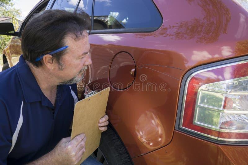 Regler, der Schaden auf Fahrzeug betrachtet stockfoto