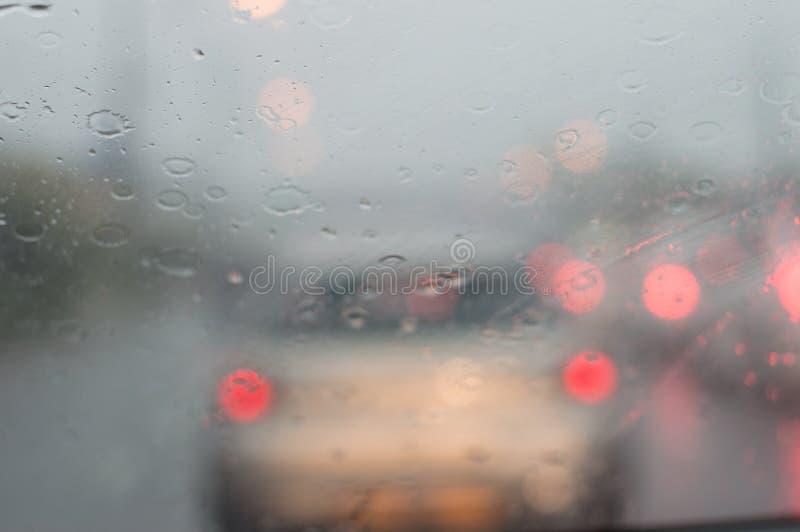 Regn och vatten i trafikstockningrött ljussuddighet arkivbilder