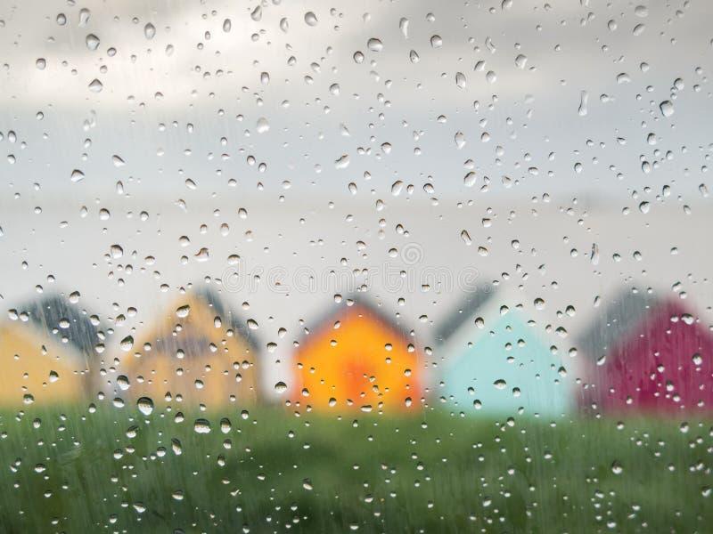 Regn tappar på ett bilfönster på en engelsk sjösidastad fotografering för bildbyråer