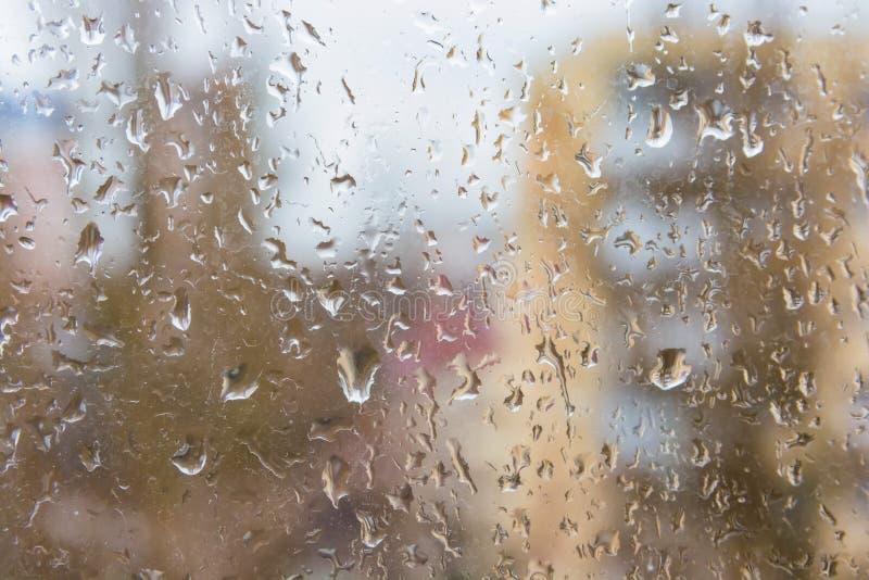 Regn tappar på yttersida för fönsterexponeringsglas med modern hyreshus i bakgrund arkivfoto