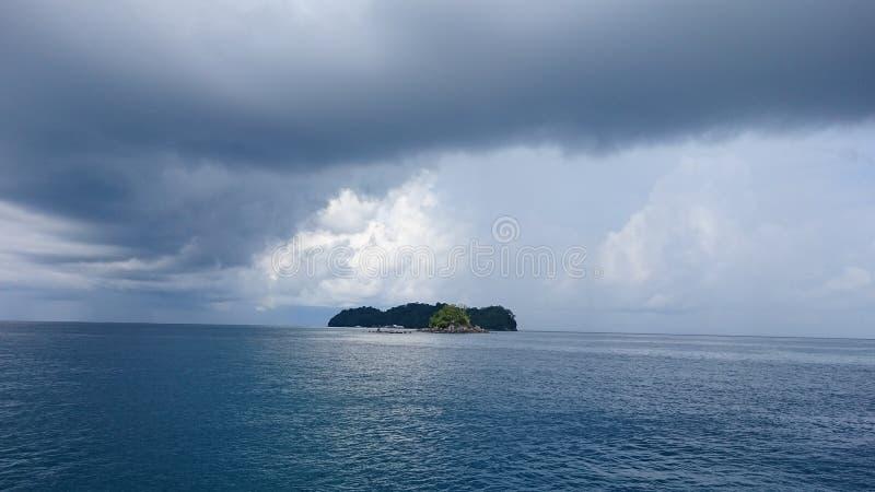 Regna den kommande mitt av havet och den lilla ön royaltyfria bilder