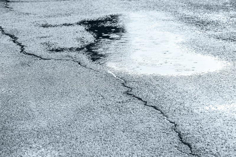 Regna pölar på våt trottoar med sprickor i stadsgata arkivbild