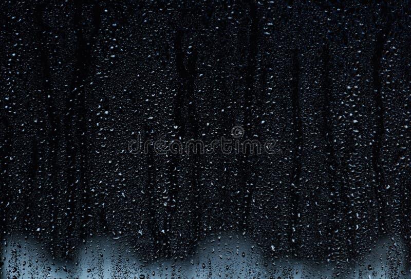 Regna små droppar som kör ner ett fönster, abstrakt bakgrund royaltyfria foton