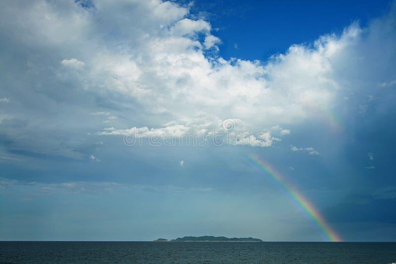 Regnbåge över ön royaltyfri fotografi