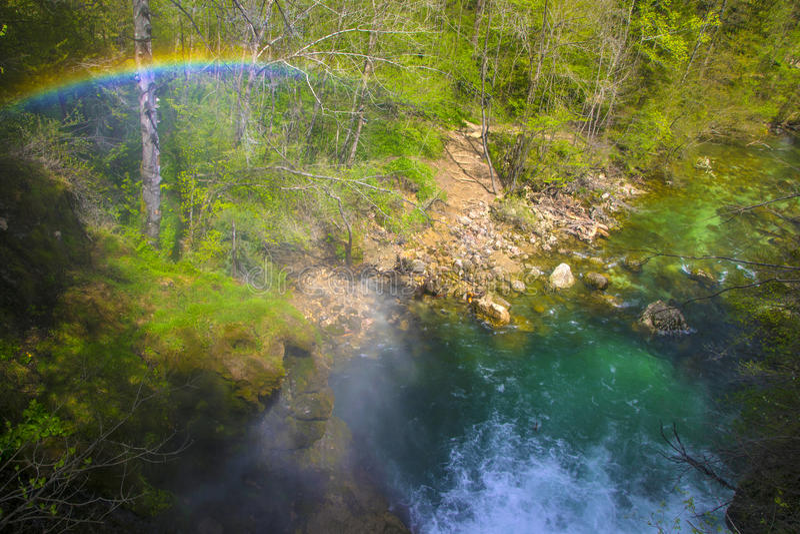 Regnbåge över bergströmmen som flödar till och med klyftan, Slovenien royaltyfria bilder