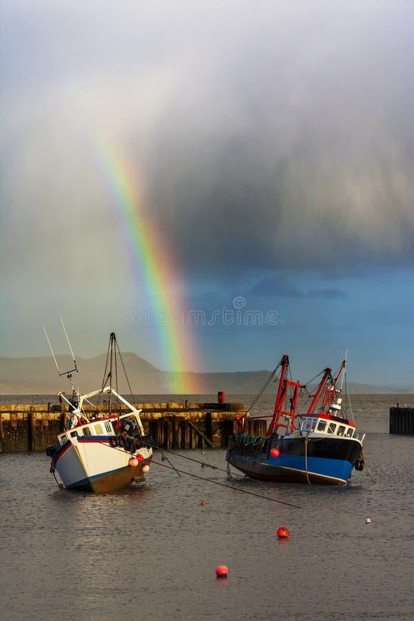 Regnbåge över fiskebåtar på Lyme Regis fotografering för bildbyråer