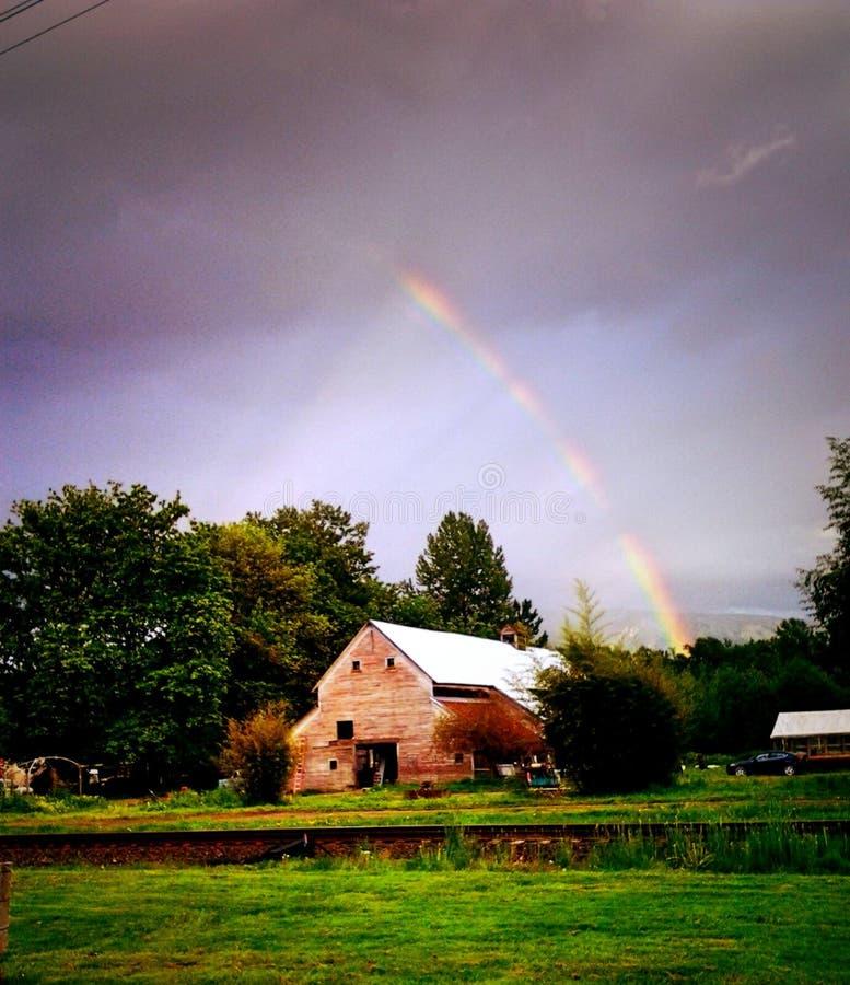 Regnbåge över landsladugård royaltyfria bilder