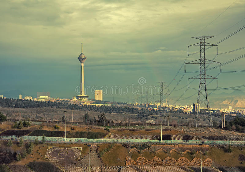 Regnbåge bredvid Milad Tower på horisont av Teheran med tappningfiltret royaltyfri fotografi