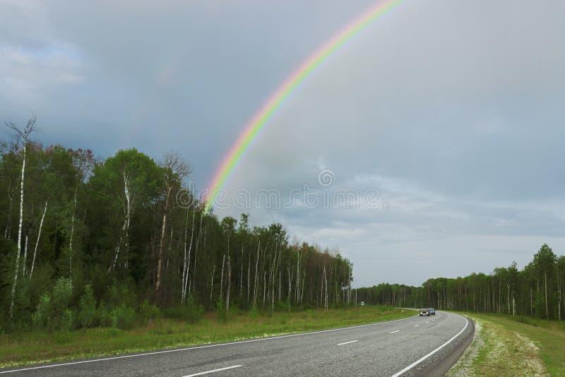Regnbåge efter regn över huvudvägen royaltyfri foto