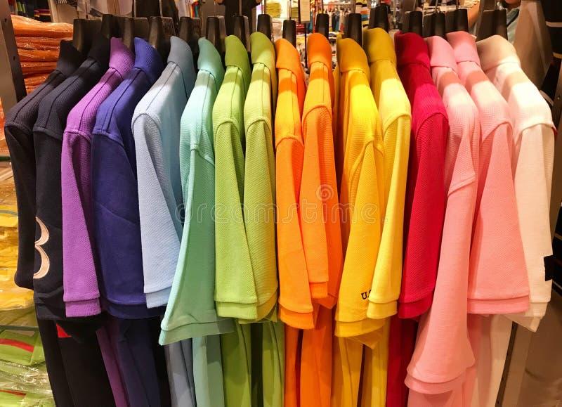 Regnbåge eller färgrika poloskjortor på hängare i shoppinggalleria arkivbilder