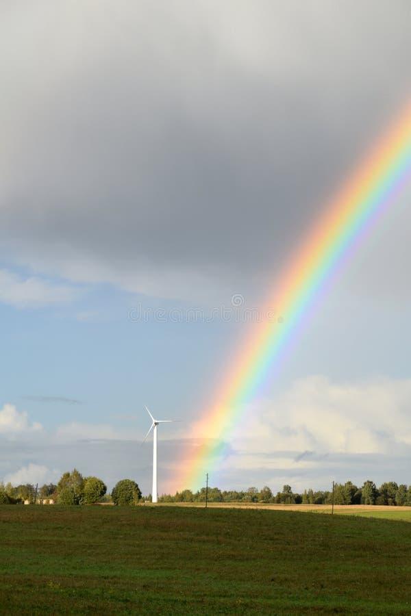 Regnbåge nära energigeneratorerna på bygd arkivbilder