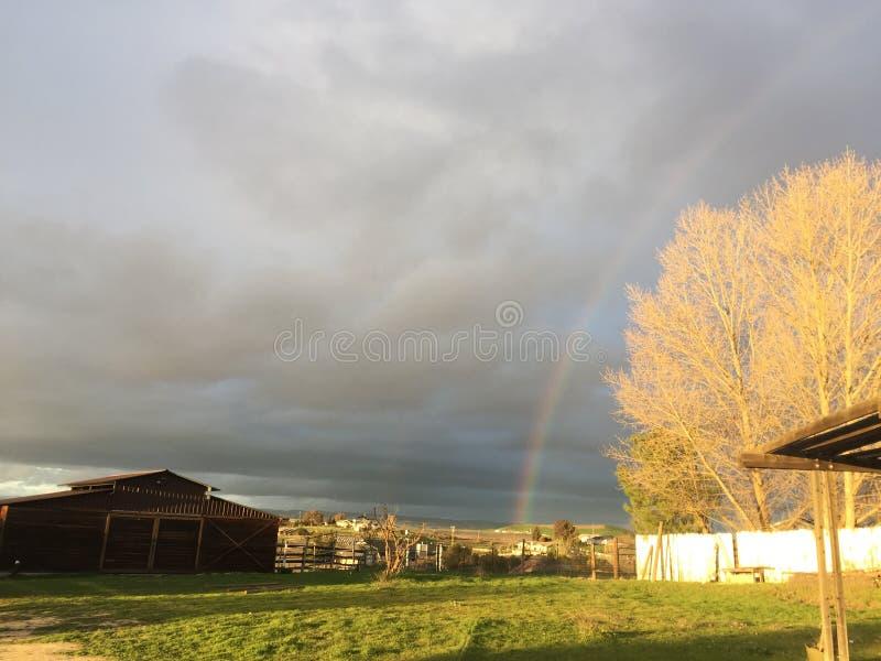 Regnbåge och ladugård med grönt gräs royaltyfria foton