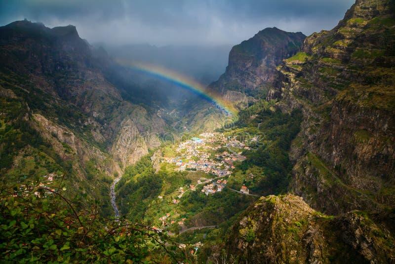 Regnbåge ovanför bergby royaltyfri foto