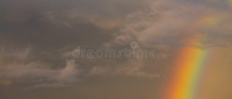 Regnbåge på solnedgången med en molnig himmel royaltyfri bild