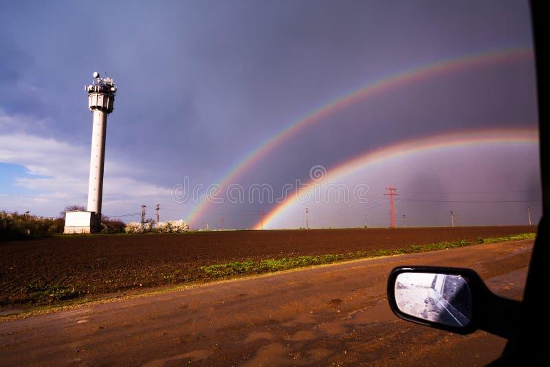 Regnbåge som ses från bilen arkivbilder