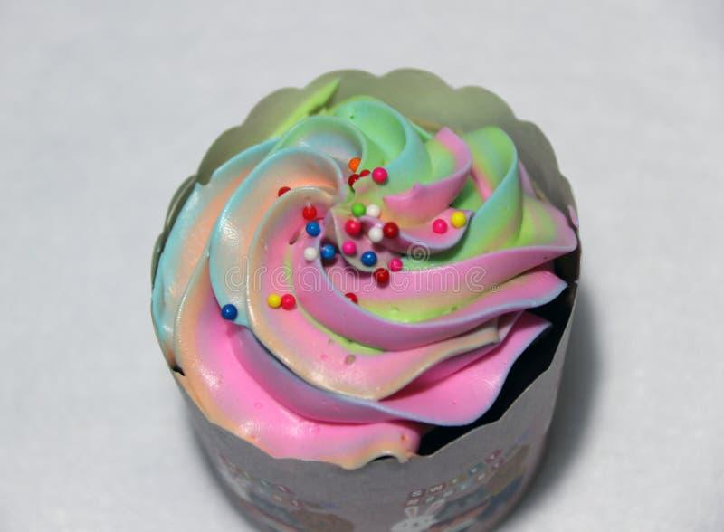 Regnbågefärg av koppkakan på den vita bakgrunden med färgrikt rundat socker pryder med pärlor på överkanten royaltyfri fotografi