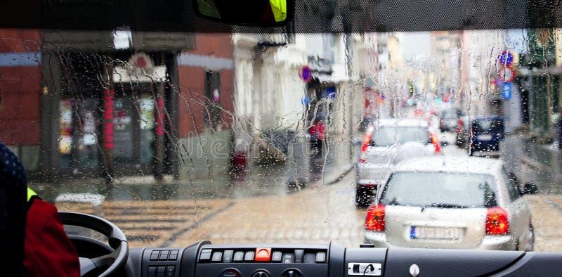 Regndroppar på chaufförbussfönstret clolful sikt på gatatrafik stads- backgruond arkivfoton