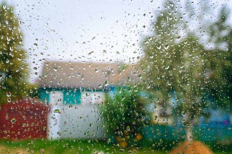 Regndroppar på ett fönsterexponeringsglas av en boning, var delen av gatan ses i bakgrunden arkivbild
