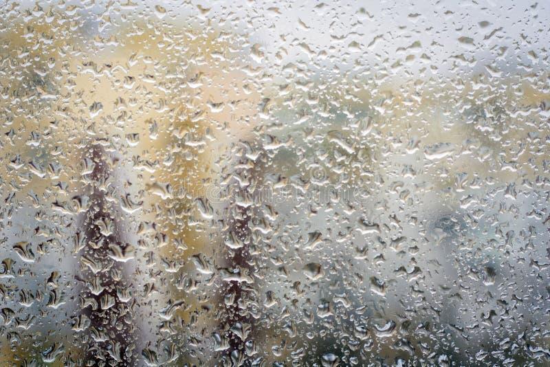 Regndroppar på exponeringsglas, fönsterbakgrundssikt av byggnader ut ur fokus arkivbild