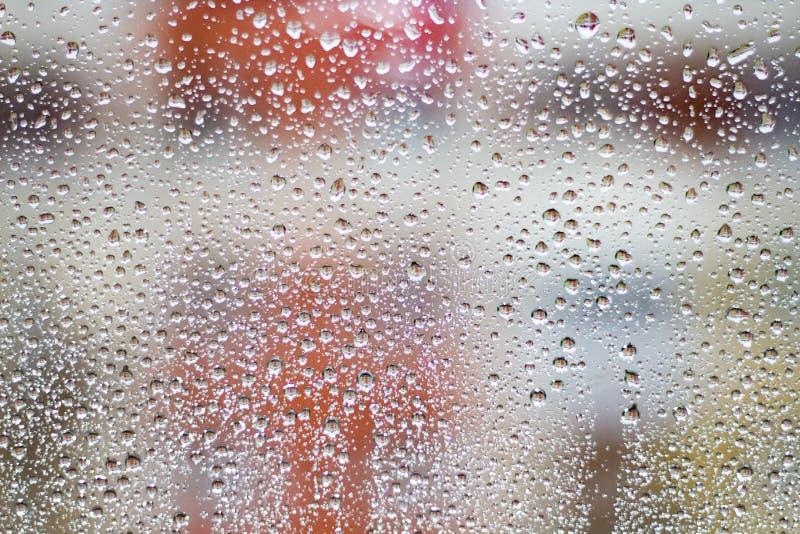 Regndroppar på exponeringsglas på suddig färgrik bakgrund royaltyfri bild