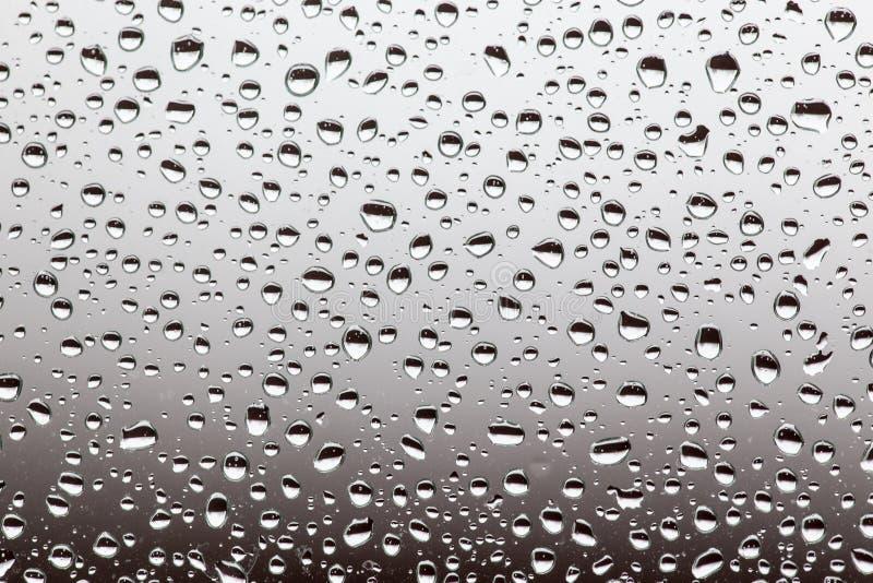 Regndroppar på exponeringsglaset, bakgrund textu för vattendroppbakgrund arkivfoto