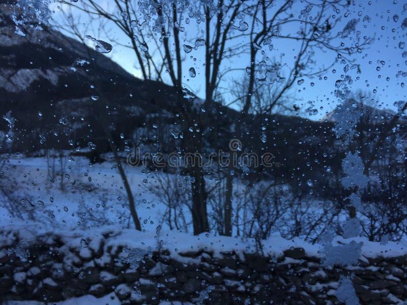 Regndroppar på exponeringsglaset i vinterlandskap arkivbilder