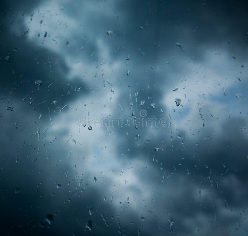 Regndroppar på fönster över moln arkivbilder