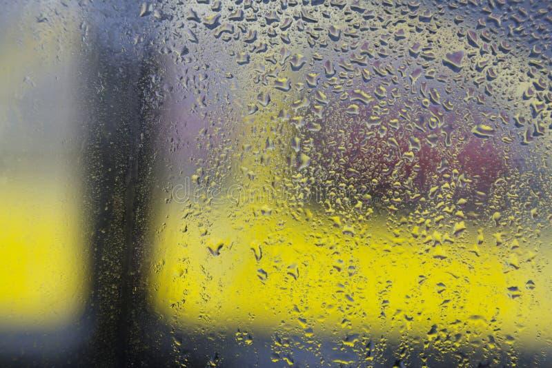 Regndroppar på fönster av bilen och bakgrund i gult och rött fotografering för bildbyråer