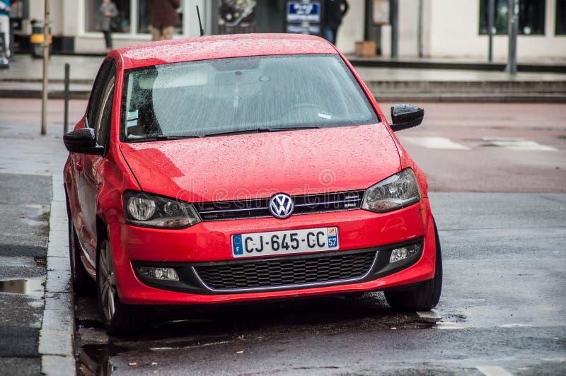Regndroppar på röd parkerad Volkswagen polo i gatan arkivfoton