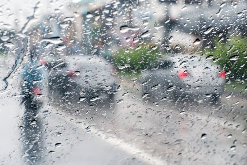 Regndroppar på vindrutan från inre bilen i trafikstockning arkivfoto