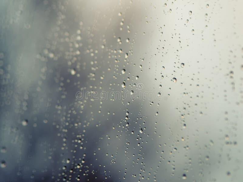 Regndroppar på yttersidan av fönsterexponeringsglas med arkivbilder