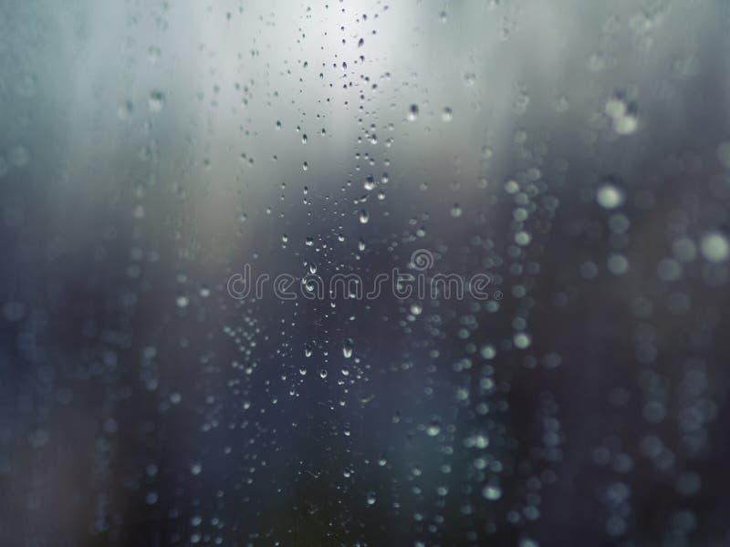 Regndroppar på yttersidan av fönsterglas royaltyfri foto
