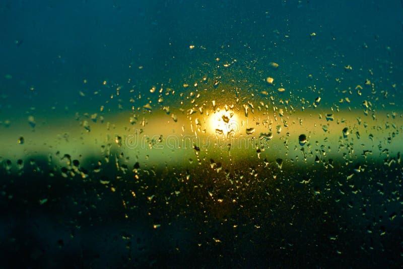 Regndropptextur på fönsterexponeringsglas med att bedöva horisont för cityscape för färgrikt för solnedgångljus för blå gräsplan  arkivbilder