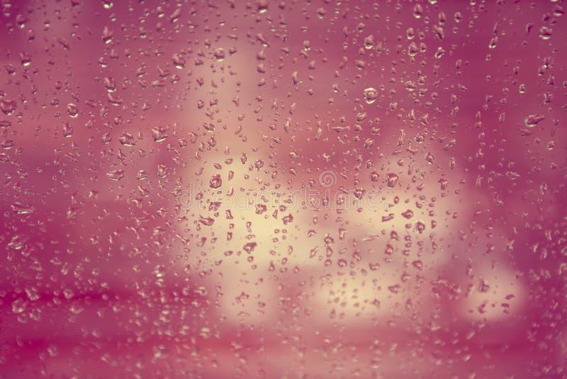 Regnen Sie Tropfen auf Fensterglas mit Unschärfebaumhintergrund, Weinlesecol. lizenzfreie stockbilder
