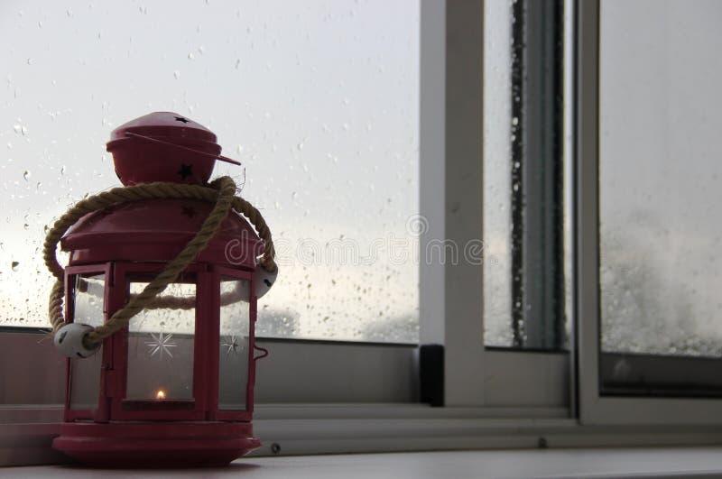 regnerischer Sommertag, Regentropfen auf dem Fensterglas, dekorative rosa Laterne mit einem brennenden Kerzeninnere, Häuser auf d lizenzfreies stockfoto