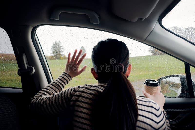 Regnerischer Tag oder schlechtes Wetter in einem Ferien-Konzept eine Traurigkeits-Frau mit dem heißen Kaffee, der im Auto sitzt u stockfoto