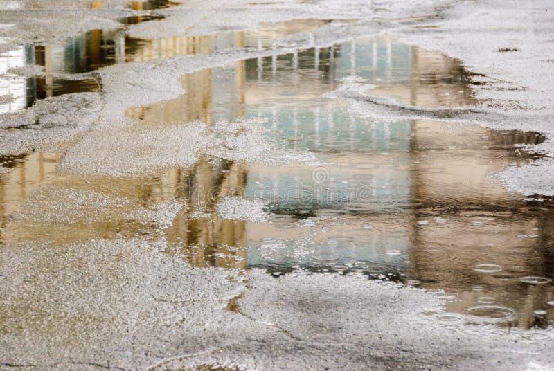 Regnerischer Tag Reflexion in der Pfütze auf der Stadtstraße während des Regens stockfotos