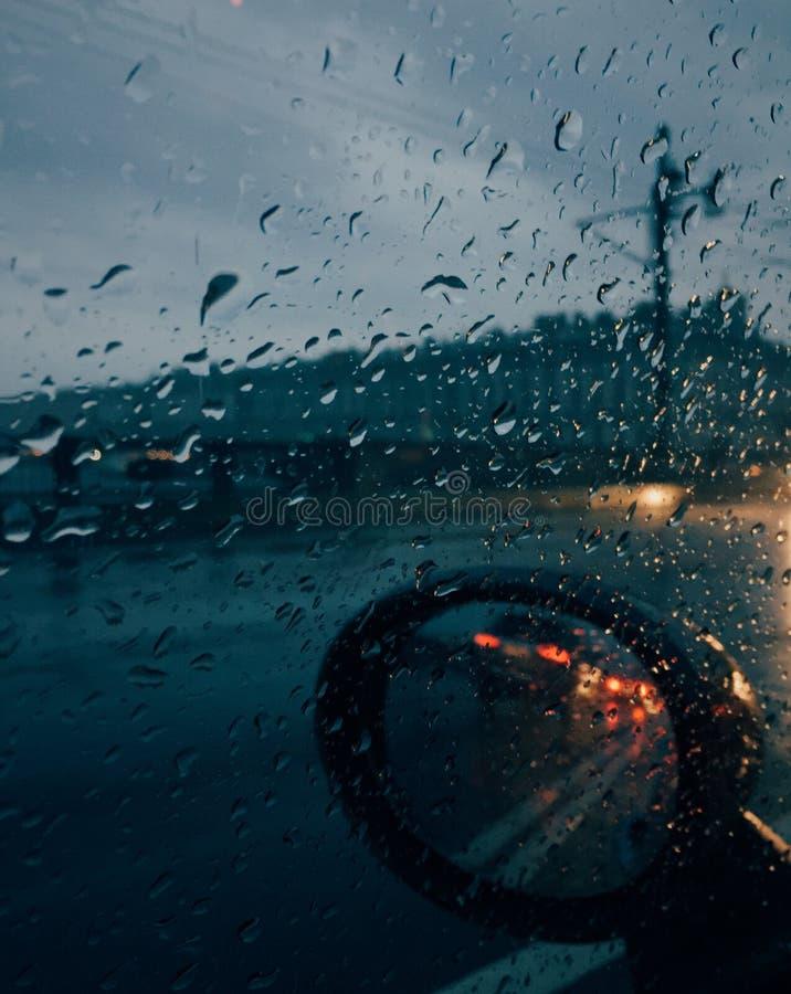 Regnerisches Wetter Raindsrops außerhalb des Autos mit Selbstspiegel, unerkennbarer Fahrer fährt Auto am schlechten Wetter währen lizenzfreies stockbild