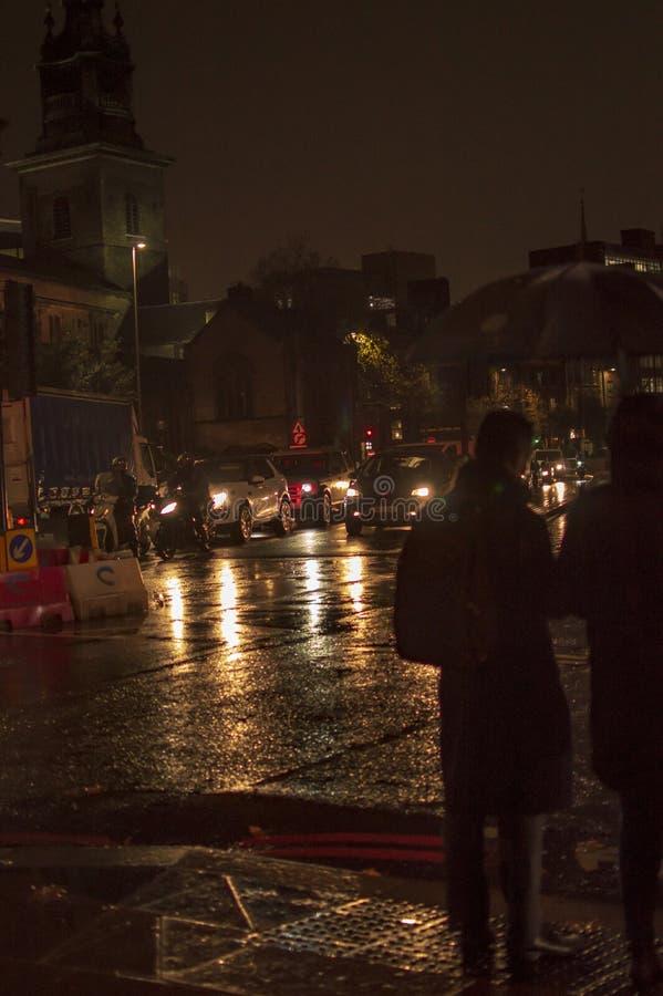 Regnet och de v?ta v?garna i london, i natt och att g? f?r folk royaltyfri foto
