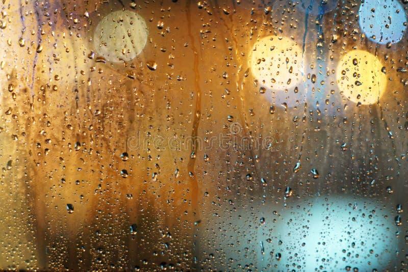 Regnet tappar på det glass fönstret med bokehbakgrund royaltyfri bild