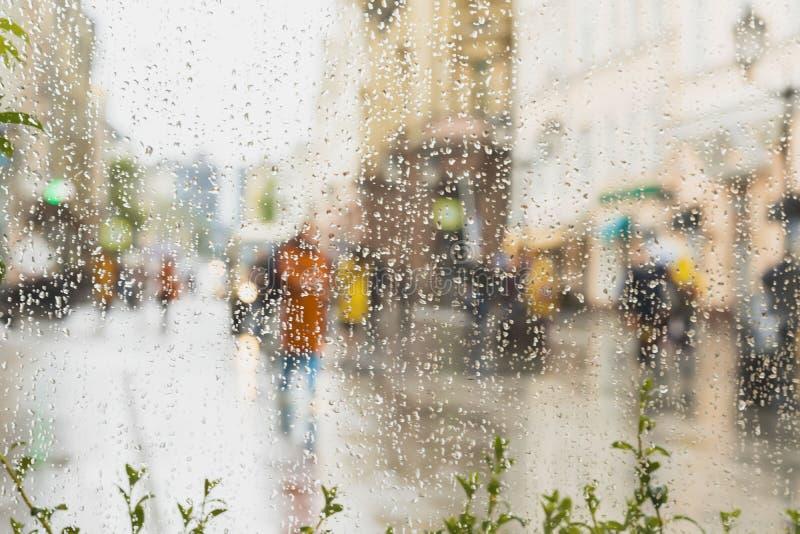 Regnig dag i stad Folk som ses till och med regndroppar på exponeringsglas Selektiv fokus på regndropparna royaltyfri foto