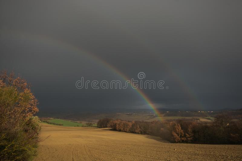 Regnig dag i Tuscany med den dubbla regnbågen, Chianciano Terme arkivfoto