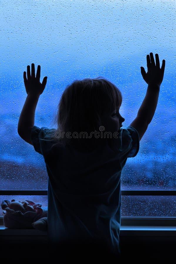 Regnig dag med lilla flickan på fönstret som ut ser fotografering för bildbyråer